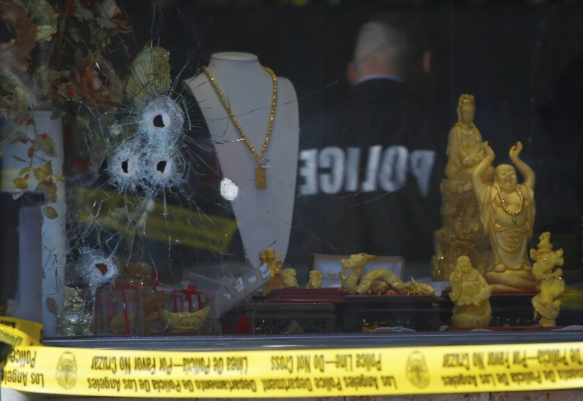 Police investigate the shooting of a security guard at a jewelry store in downtown L.A.'s Chinatown earlier this year. Paramedics treated the man for an arm wound, according to reports from the scene.