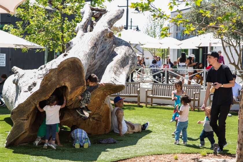 Children play on a giant log structure at the center of One Paseo urban village in Carmel Valley.
