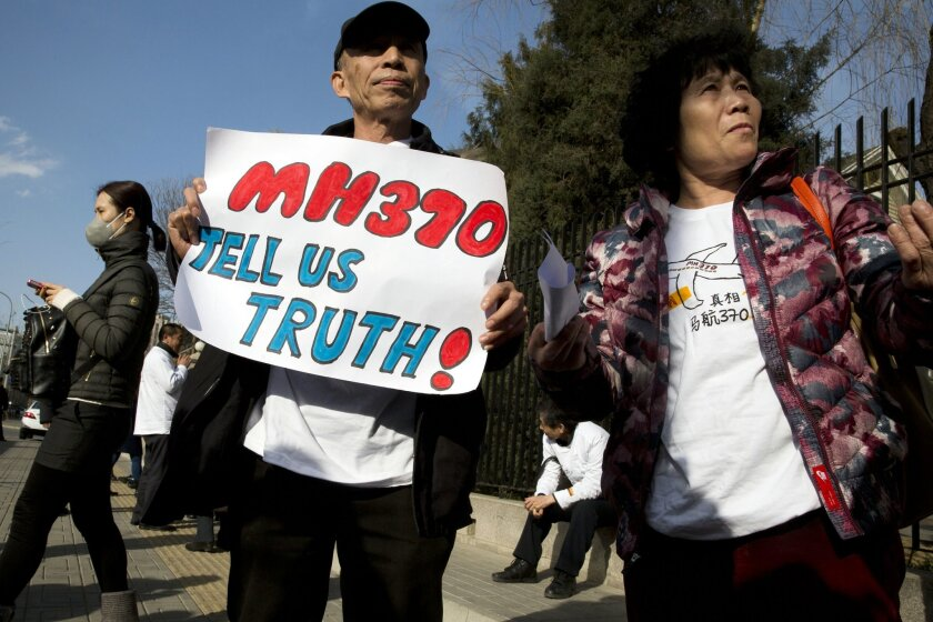 Relatives of passengers on board the missing Malaysia Airlines Flight 370 protest near the Malaysian Embassy in Beijing on the one year anniversary, Sunday, March 8, 2015. Families of the 239 people on board the plane on Sunday marked the anniversary of the plane's disappearance, vowing to never gi