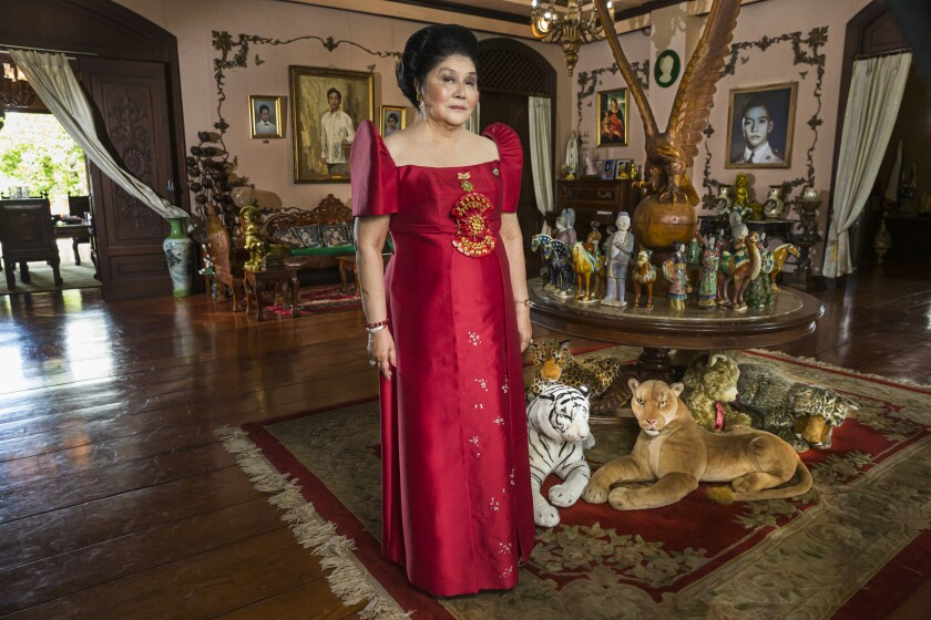 "Imelda Marcos, wearing a red dress, in the movie ""The Kingmaker."""