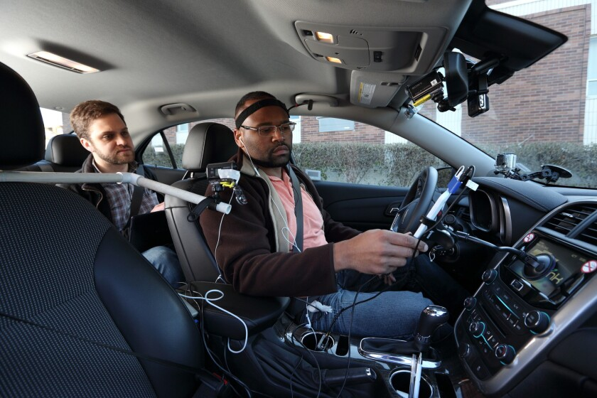Research assistants introduce study participants to special devices designed to gauge mental distraction during road tests conducted by AAA and the University of Utah.