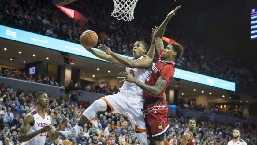 Virginia's Devon Hall (0) goes past Louisville defender Ray Spalding (13) for a basket on Feb. 6.