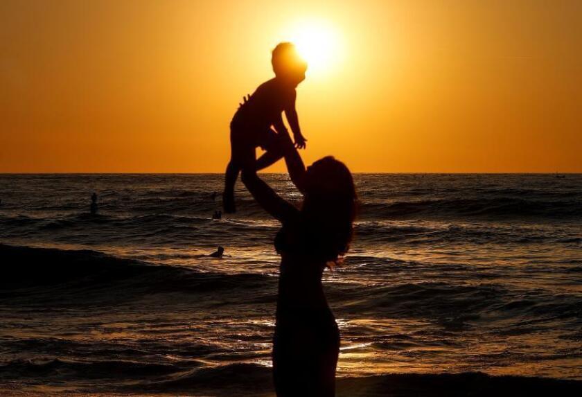 Una mujer y su hijo disfrutan del atardecer en la playa de La Zurriola, en San Sebastián. EFE/Archivo