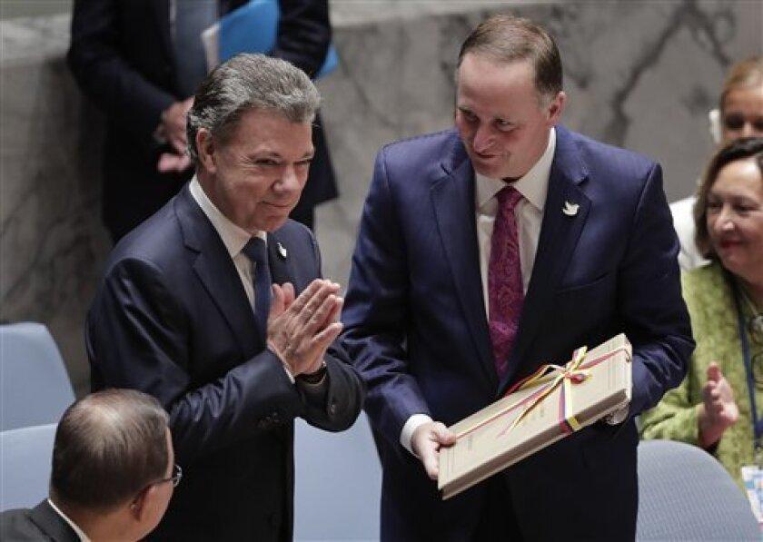 El presidente de Colombia Juan Manuel Santos (izq) agradece los aplausos de los integrantes del Consejo de Seguridad de la ONU tras entregarle al presidente de ese cuerpo Jon Ker una copia de los acuerdos de paz entre su gobierno y las FARC el 21 de septiembre del 2016.