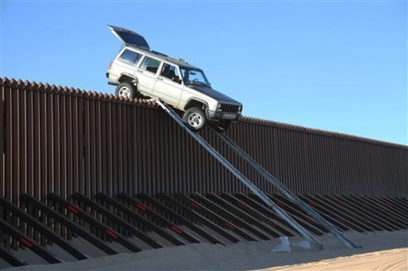 In this photo provided by the U.S. Customs and Border Protection, a silver Jeep Cherokee that suspected smugglers were attempting to drive over the U.S.-Mexico border fence is stuck at the top of a makeshift ramp early Wednesday, Oct. 31, 2012 near Yuma, Ariz. U.S. Border Patrol agents from the Yuma Station seized both the ramps and the vehicle, which stalled at the top of the ramp after it became high centered. The fence is approximately 14 feet high where the would-be smugglers attempted to illegally drive across the border. The two suspects fled into Mexico when the agents arrived at the scene. (AP Photo/U.S. Customs and Border Protection)