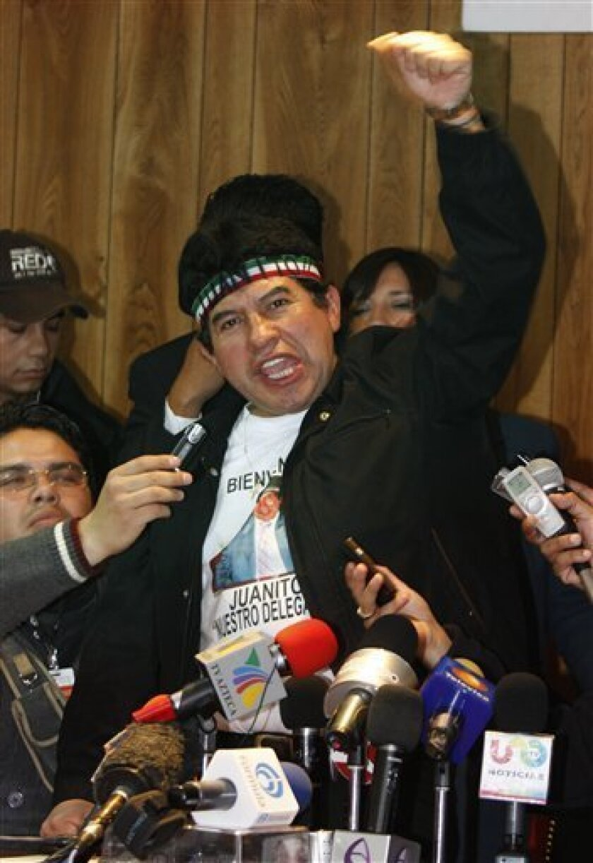 "Rafael Acosta gestures during a press conference in Mexico City's Ixtapalapa borough, Monday, Nov. 30, 2009.  Acosta, better known for his nickname ""Juanito"" and his Rambo-style headband, has taken over the offices of Mexico City's most populous borough and says ""the only way they'll get me out is"