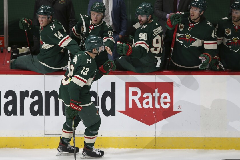 Minnesota Wild's Nick Bonino (13) high fives teammates on the bench in celebration after scoring a goal against the San Jose Sharks, during the first period of an NHL hockey game Friday, April 16, 2021, in St. Paul, Minn. (AP Photo/Stacy Bengs)
