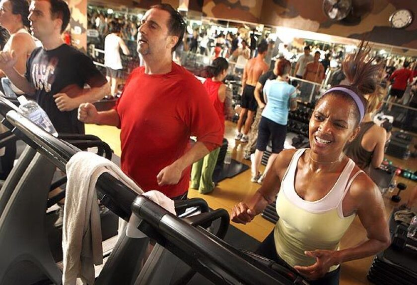 Sean Bello, center, and Rhonda Smith, right, push themselves on the treadmill while others behind them work out with exercises on the floor at Barry's Boootcamp in West Hollywood. The boot camp programs at Barry's and other gyms help people to kick start their New Year's fitness programs.