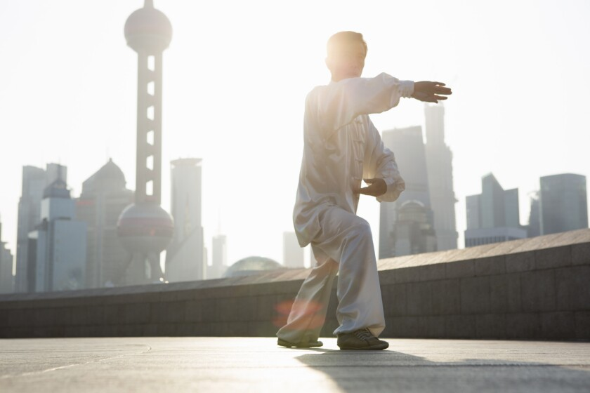Chinese man practicing Tai Chi in the morning.