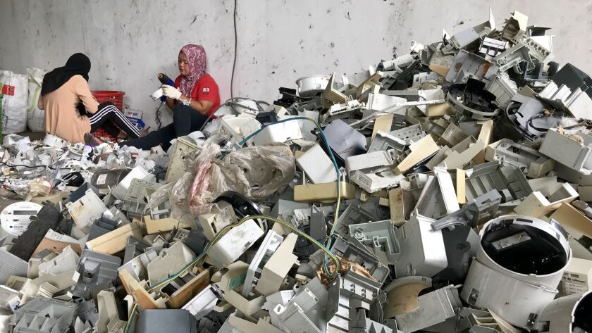 Workers dismantle plastic waste from the U.S. and other countries at a warehouse in Port Klang, Malaysia.