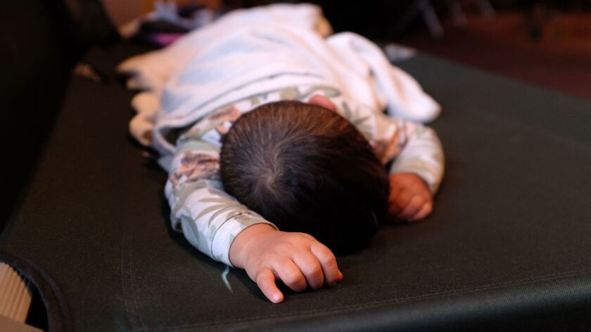November 19, 2018_|A small child sleeps on a cot at the temporary shelter.|A temporary migrant shelt