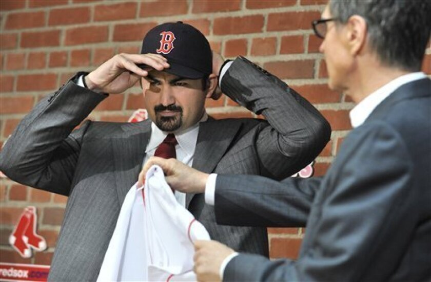 New Boston Red Sox first baseman Adrian Gonzalez, left, pulls on his team cap as team owner John Henry, right, holds out his new jersey during a news conference at Fenway Park in Boston, Monday, Dec. 6, 2010. ,(AP Photo/Josh Reynolds)
