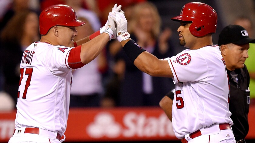 Angels center fielder Mike Trout (27) congratulates teammate Albert Pujols (5) after he hit a two-run home run against the Astros on Friday night.