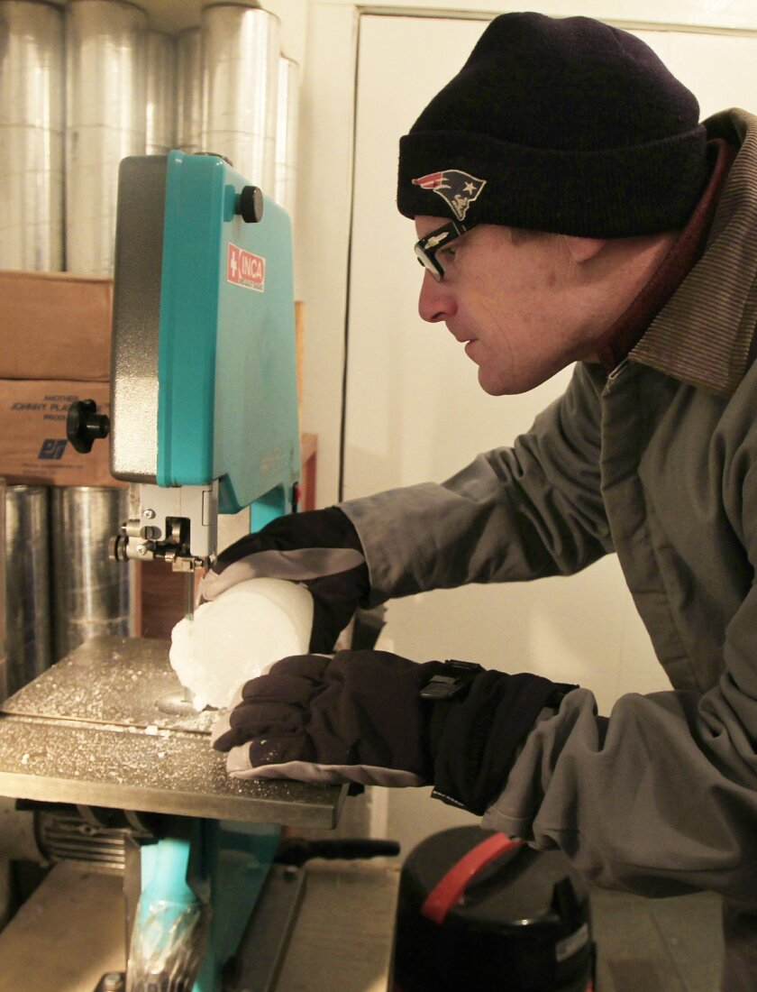 Stored in a -7F basement, Dr. Jeff Severinghaus, a professor of geosciences at Scripps Institution of Oceanography, cuts an ice core with trapped bubbles of gases he studies to track changes in ancient climate at Scripps on Friday in San Diego, California.