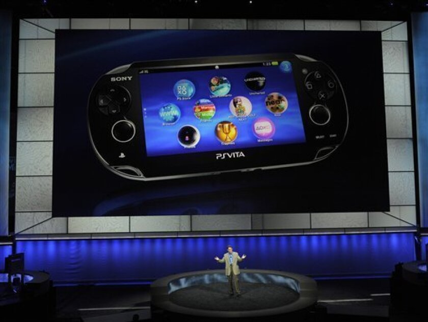 Kazuo Hirai, bottom, President and Chief Executive of Sony Computer Entertainment America, introduces the company's next generation portable gaming machine, Playstation Vita, during a news conference at the E3 Gaming Convention in Los Angeles, Monday, June 6, 2011. (AP Photo/Chris Pizzello)