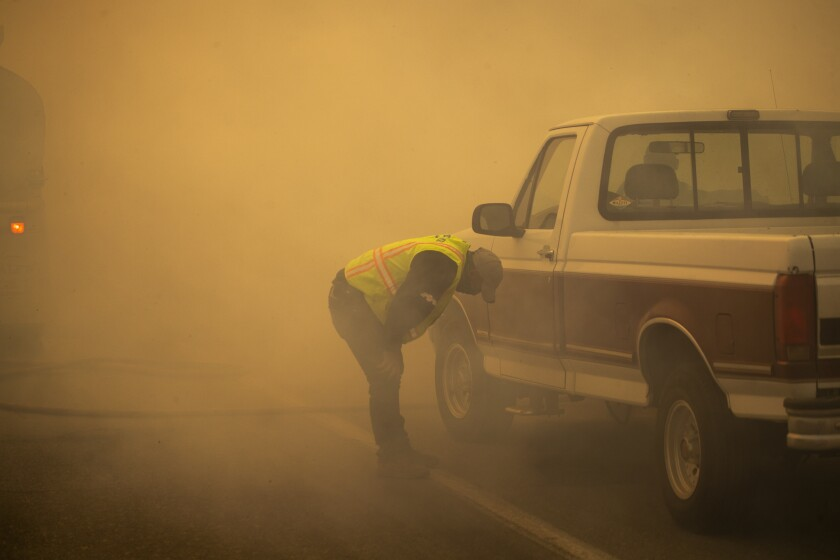 A water truck operator is overcome with smoke after running through the advancing Silverado fire in Orange County.