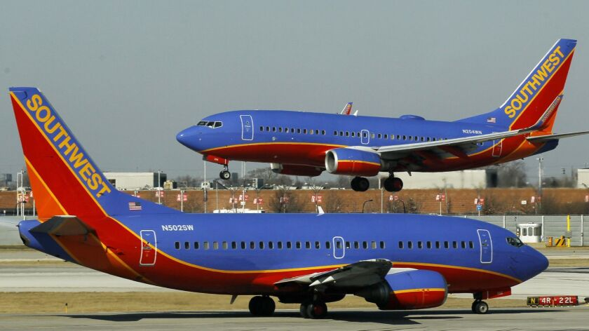 A Southwest Airlines Boeing 737 waits to take off at Chicago's Midway Airport as another lands. The Dallas-based carrier plans to begin selling tickets to flights to four airports in Hawaii later this year from Oakland, San Diego, San Jose and Sacramento.