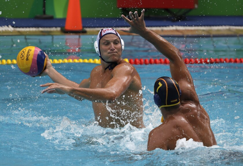 Jesse Smith looks to pass the ball during a water polo match.