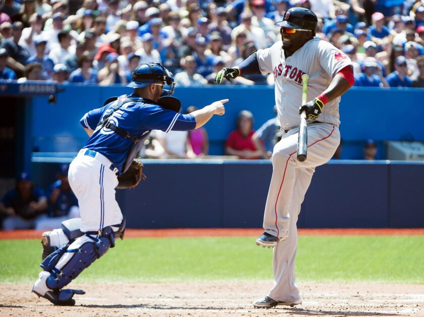 Boston Red Sox designated hitter David Ortiz (34) reacts after apparently taking a foul ball to his leg as Toronto Blue Jays catcher Russell Martin (55) looks on during the fifth inning of baseball game in Toronto, Saturday, May 28, 2016. (Nathan Denette/The Canadian Press via AP) MANDATORY CREDIT