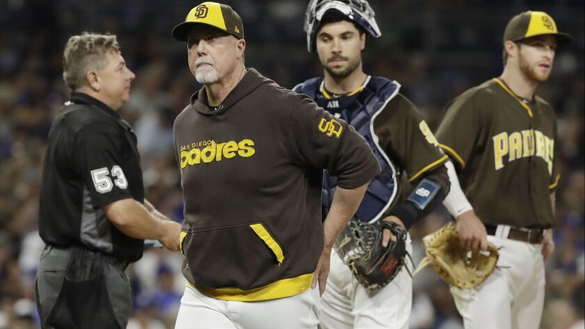 San Diego Padres bench coach Mark McGwire, front, walks back to the dugout after making a pitching change during the fourth inning of the team's baseball game against the Los Angeles Dodgers on Friday, June 30, 2017, in San Diego.