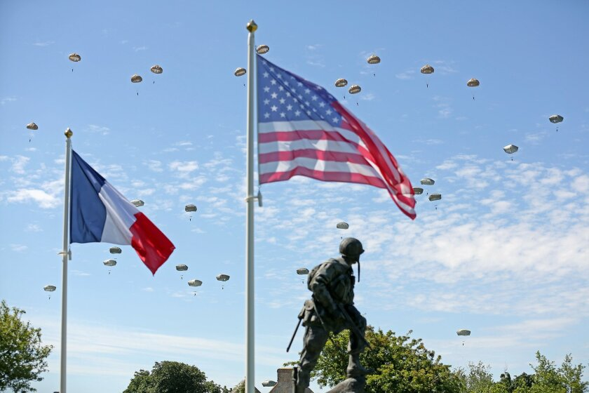 Paratroopers are dropped near the Normandy village of Sainte Mere Eglise, western France, during a mass air drop, Sunday June 8, 2014, as part of commemorations of the 70 anniversary of the D-Day landing. World leaders and veterans gathered by the beaches of Normandy on Friday to mark the 70th anniversary of the World War II D-Day landings. Visible at foreground is bronze sculpture Iron Mike, a monument dedicated to the American airborne soldiers who fought on the D Day.(AP Photo/Remy de la Mauviniere)