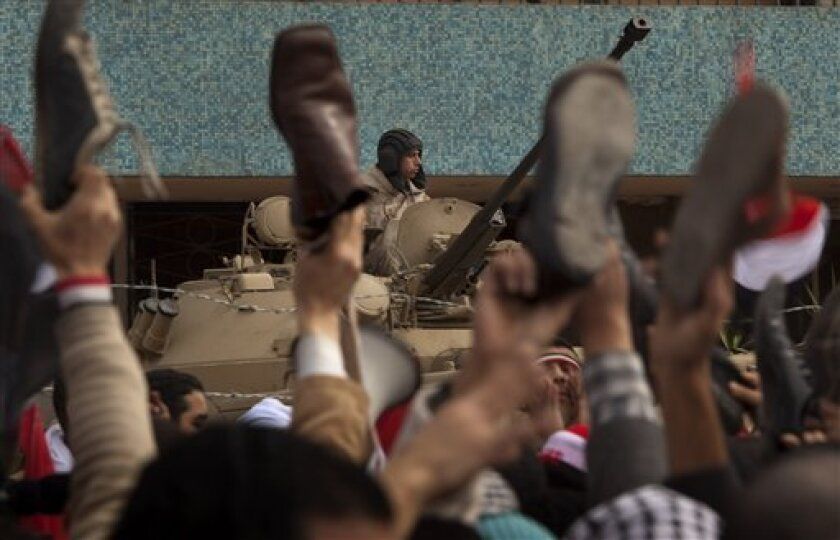 An army soldier sits on a armored vehicle as anti-government protesters hold their shoes in the air during a protest in front of  the state television building on the Corniche in downtown Cairo, Egypt Friday, Feb. 11, 2011. Mubarak refused to step down or leave the country and instead handed his po