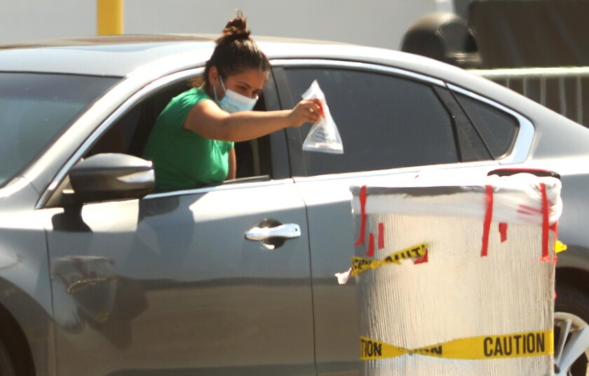 A woman deposits her coronavirus test in a bin at the COVID-19 testing site at the Forum parking lot in Inglewood.