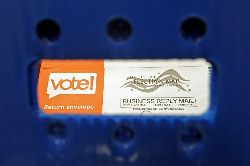 FILE - In this Aug. 5, 2020, file photo a vote-by-mail ballot is shown as viewed through the handle of a sorting tray at the King County Elections headquarters in Renton, Wash., south of Seattle. The Centers for Disease Control recommends mail ballots as a way to vote without risking exposure to the virus at the polls. Washington has had vote by mail since 2011. (AP Photo/Ted S. Warren, File)