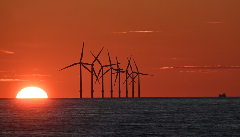 The sun sets behind wind turbines at sea, lending an orange glow to the sky