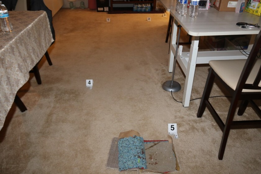 In a carpeted room, numbered tags on the floor mark pieces of evidence.