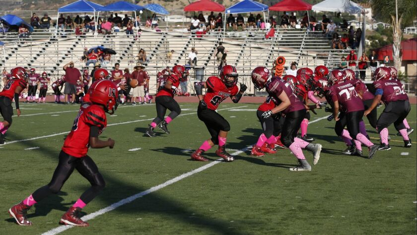 Players from Pee Wee football league featuring Spring Valley Los Toros (Maroon and Black) vs. Imperial Beach Chiefs (red and black).