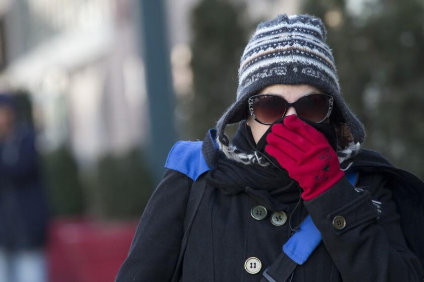 Una mujer se coloca la bufanda sobre la nariz y la boca para protegerse del frío, en Nueva York. (Foto AP/Mary Altaffer)