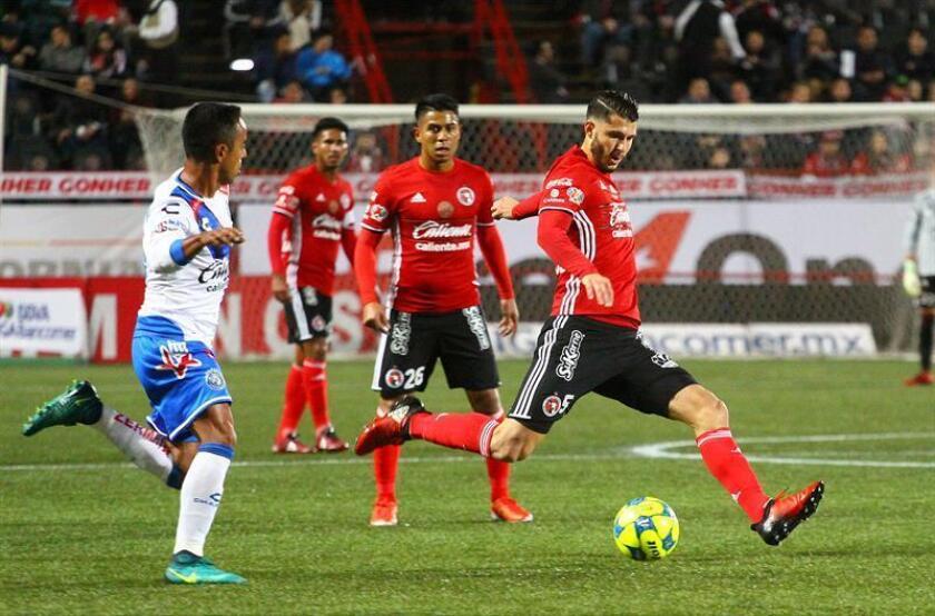 El jugador Guido Rodríguez (d) de Xolos Tijuana disputa el balón con Francisco Torres (i) de Puebla. EFE/Archivo