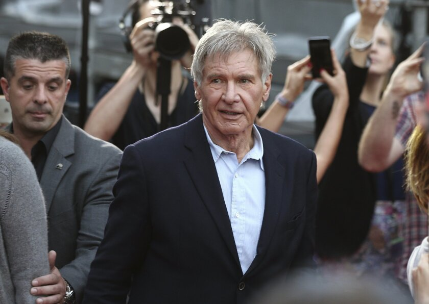 """FILE - In this December 10, 2015 file photo Harrison Ford walks during a Star Wars fan event in Sydney. Ford is in Australia to promote his latest film """"Star Wars: The Force Awakens"""". British health authorities said on Thursday Feb. 11, 2016 that criminal charges have been laid against producers of"""