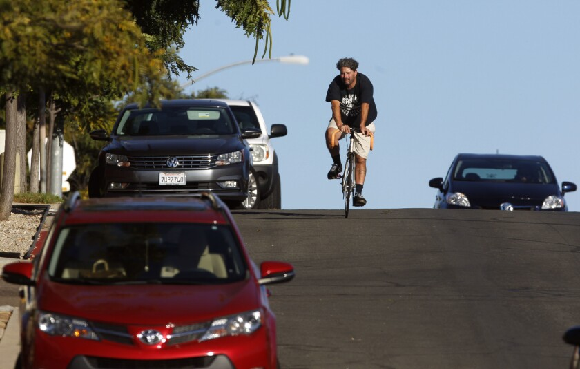 A bicyclist rides down a San Diego street. The city is planning to remove parking on some streets to make way for protected bike lanes.