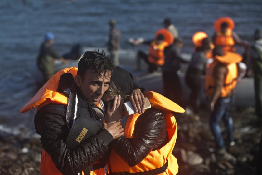A man hugs his spouse after travelling by boat to a beach on the northern shore of Lesbos, Greece, Saturday, Nov. 7, 2015. Well over half a million people have reached the Greek islands so far this year, a record number of arrivals, and the journey has proved fatal for hundreds. (AP Photo/Marko Dro