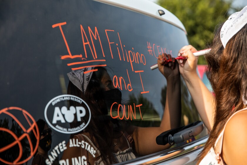 Alexis Hernandez, 18, writes on back window of an SUV, promoting the 2020 Census.