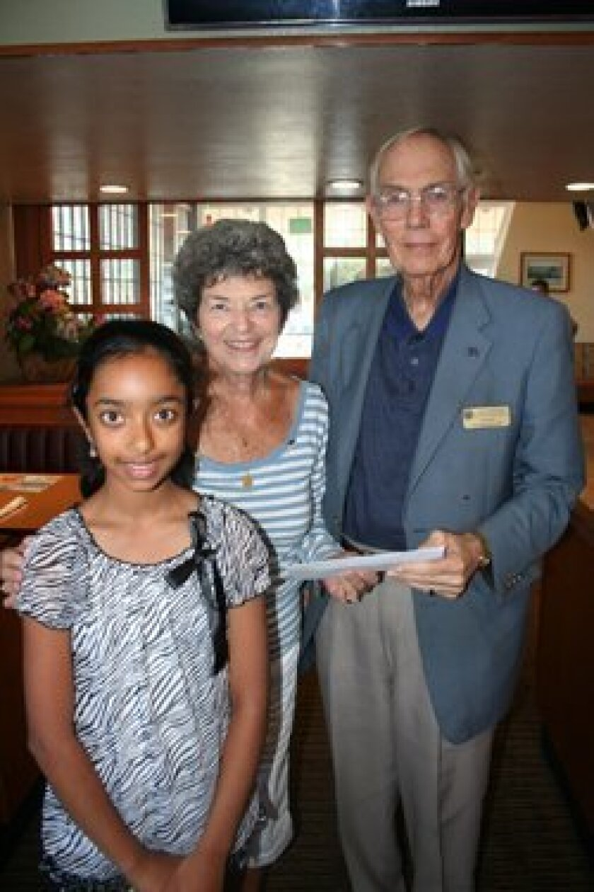 Anjali Haripriyan donated $340 to the Del Mar/Solana Beach Optimist Club's Rady Children's Cancer Fund. Accepting her gift were Optimist Susan Pfleeger and President Dave Eller. Photo/K. Billing