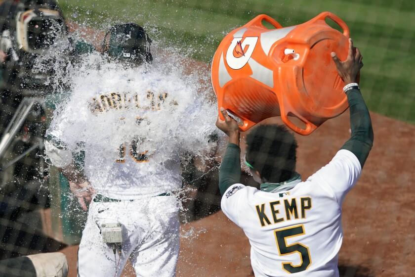 Tony Kemp vacía la hielera encima de Mitch Moreland, su compañero en los Atléticos de Oakland, quien remolcó la carrera del triunfo sobre los Dodgers de Los Ángeles, el miércoles 7 de abril de 2021 (AP Foto/Jeff Chiu)