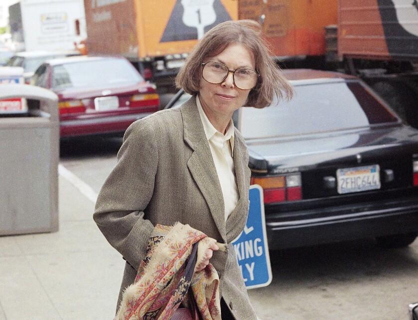 Janet Malcolm looks at the camera as she walks across a sidewalk near cars.