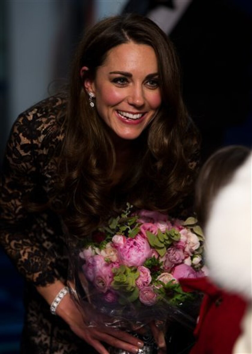 The Duchess of Cambridge talks to a guest after being presented with her bouquet as she arrives for the UK Premiere of 'War Horse' in aid of The Foundation of Prince William and Prince Harry, at a central London cinema, London, Sunday, Jan. 8, 2012. (AP Photo/Ian Gavan, Pool)