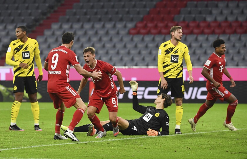Bayern Munich's Joshua Kimmich, center left, celebrates scoring his side third goal during the German Bundesliga Supercup soccer match between FC Bayern Munich and Borussia Dortmund in Munich, Germany, Wednesday, Sept. 30, 2020. (Sven Hoppe/Pool via AP)