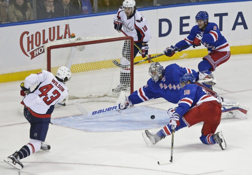 New York Rangers goalie Henrik Lundqvist (30), of Sweden stops a shot by Washington Capitals' Tom Wilson (43) as teammates Marc Staal (18) and Kevin Klein (8) watch during the third period of an NHL hockey game Tuesday, Nov. 3, 2015, in New York. The Rangers won 5-2. (AP Photo/Frank Franklin II)