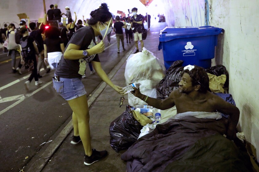 A protester hands a homeless man a bottle of water.