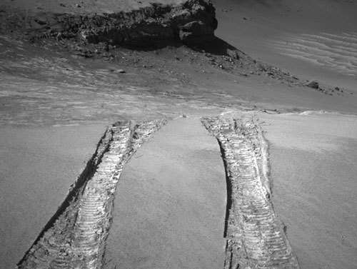 The Mars rover Opportunity climbed out of Victoria Crater on Aug. 28, following the tracks it had made when it descended into the half-mile-diameter bowl nearly a year earlier. The rover's navigation camera captured this view back into the crater just after finishing a 22-foot drive onto level ground.