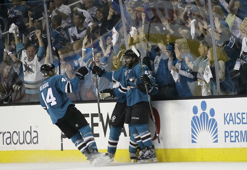 San Jose Sharks right wing Joel Ward, right, celebrates with teammates after scoring against the Pittsburgh Penguins during the third period of Game 3 of the NHL hockey Stanley Cup Finals in San Jose, Calif., Saturday, June 4, 2016. (AP Photo/Marcio Jose Sanchez)