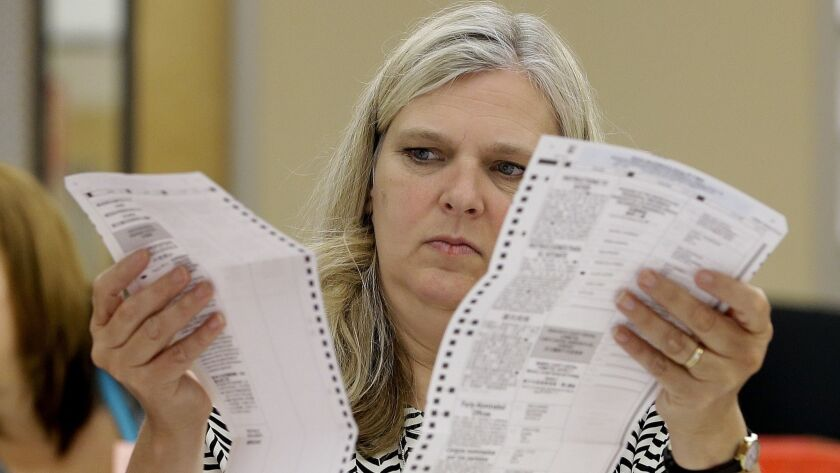 Allison Benton a temporary worker at the Sacramento County Registrar of Voters office, inspects a ma