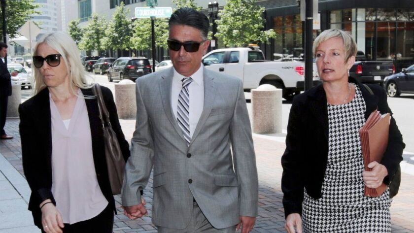 Former USC women's soccer coach Ali Khosroshahin, center, arrives at federal court Thursday to plead guilty to charges in a nationwide college admissions bribery scandal.