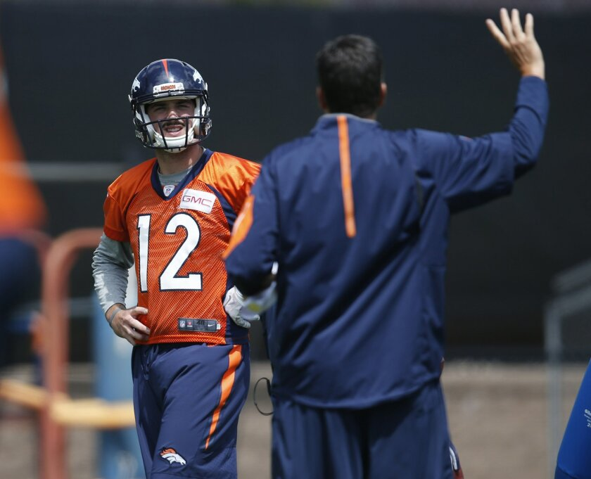 Denver Broncos rookie quarterback Paxton Lynch, back, is directed by quarterbacks coordinator Greg Knapp during NFL football practice Tuesday, May 31, 2016, at the team's headquarters in Englewood, Colo. (AP Photo/David Zalubowski)
