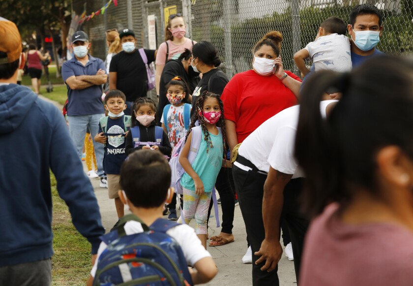 Masked parents and children lined up outside a fence at an elementary school
